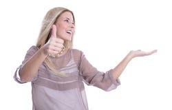 Blonde lokalisierte Frau in der beige Bluse und im Daumen oben mit seitlich Stockfotos