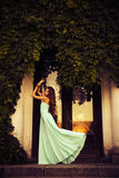 Blonde with a long curly hair in a long evening dress in motion outdoors near retro vintage building all in leaves in summer sunse Royalty Free Stock Images
