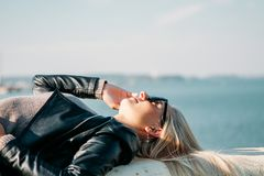 Blonde with long hair and a black leather jacket lies on the shore of the blue sea stock photography