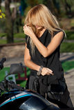 Blonde with long hair near motorcycle Stock Photos