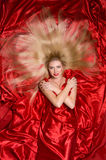 Blonde with long hair on red fabric Royalty Free Stock Image