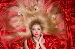 Blonde with long hair on red fabric Royalty Free Stock Images