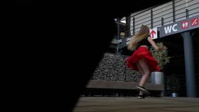 Blonde with long hair in a red skirt and a black topic makes twine in the dance in the middle of a shopping center, the stock video
