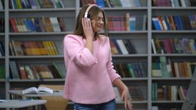 Beautiful woman in headphones having fun of music. Blonde and long-haired caucasian female student in pink sweater dancing while listening music in bluetooth