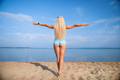 Blonde long haired girl in a blue suit is stretching and doing yoga on a lovely beach in sunlight of the rising sun. Blonde long haired girl in a blue suit is Royalty Free Stock Images