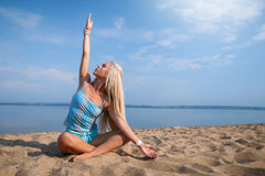 Blonde long haired girl in a blue suit is stretching and doing yoga on a lovely beach in sunlight of the rising sun. Blonde long haired girl in a blue suit is Royalty Free Stock Photos