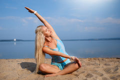 Blonde long haired girl in a blue suit is stretching and doing yoga on a lovely beach in sunlight of the rising sun. Blonde long haired girl in a blue suit is Royalty Free Stock Image