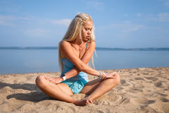 Blonde long haired girl in a blue suit is stretching and doing yoga on a lovely beach in sunlight of the rising sun. Blonde long haired girl in a blue suit is Stock Photo