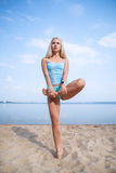 Blonde long haired girl in a blue suit is stretching and doing yoga on a lovely beach in sunlight of the rising sun. Blonde long haired girl in a blue suit is Royalty Free Stock Photo