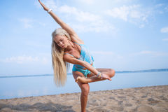 Blonde long haired girl in a blue suit is stretching and doing yoga on a lovely beach in sunlight of the rising sun. Blonde long haired girl in a blue suit is Stock Photos