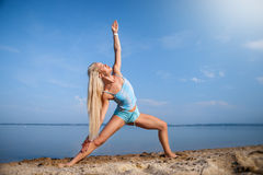 Blonde long haired girl in a blue suit is stretching and doing yoga on a lovely beach in sunlight of the rising sun Royalty Free Stock Images
