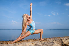 Blonde long haired girl in a blue suit is stretching and doing yoga on a lovely beach in sunlight of the rising sun Royalty Free Stock Photos