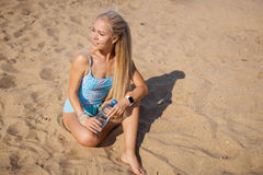 Blonde long haired girl in a blue suit is stretching and doing yoga on a lovely beach in sunlight of the rising sun Royalty Free Stock Photo