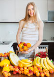 Blonde long-haired girl with heap of various fruits Royalty Free Stock Photo
