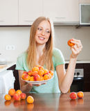 Blonde long-haired woman eating apricots in home kitchen Stock Photo