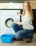 Blonde long-haired woman using washing machine at home Royalty Free Stock Images