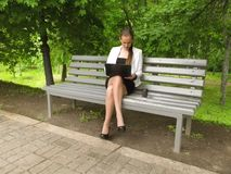Blonde long-haired young woman in office clothes sits on a bench in the park with a laptop and coffee. The concept of working with. Technology outdoors royalty free stock image