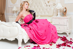 Blonde in long red dress is sitting on the bed with  roses Royalty Free Stock Images