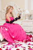 Blonde in long red dress is sitting on the bed with  roses Royalty Free Stock Photography