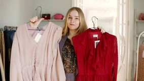 Blonde longhaired girl playfully choosing between pink and red blouse on hangers comparing them in front of a mirror. Deciding what to buy. Smiling, cheerful stock video footage