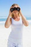 Blonde looking through binoculars on the beach Royalty Free Stock Images