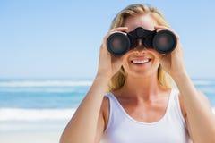 Blonde looking through binoculars on the beach Stock Photos