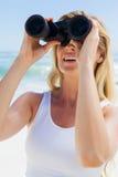 Blonde looking through binoculars on the beach Royalty Free Stock Photos
