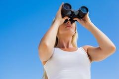 Blonde looking through binoculars on the beach Stock Images