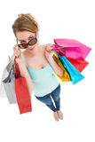 Blonde looking over her sunglasses while holding bags Royalty Free Stock Image