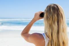 Blonde looking to the ocean through binoculars Stock Photo