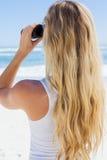 Blonde looking to the ocean through binoculars Royalty Free Stock Photos