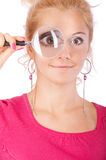 Blonde looks through magnifier Stock Images
