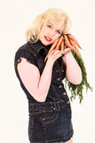 Blonde is in love with carrots Royalty Free Stock Image