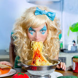 Blonde lustige auf der Küche, die Teigwaren isst, mögen verrückt Lizenzfreies Stockfoto