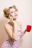 Blonde lustige Pinupfrau mit den grünen Augen u. Lockenwicklern, die über bewegliche glückliche lächelnde u. schauende Kamera spre Stockbilder