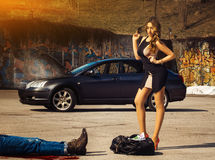 Blonde luxury woman stand over bag full of money amin fuming car Stock Photos