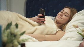 Blonde lying in bed typing a message on your phone. Soft panorama stock video footage