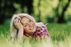 Blonde lying on green grass Royalty Free Stock Images
