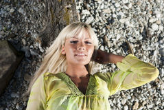 Blonde lying on a log and looking at the camera Royalty Free Stock Images