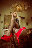 Blonde lying on a table with heels and stockings Stock Photo