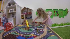 Blonde Mädchengebäude-Spielzeugeisenbahn in der Innenspielplatzspielmitte stock video footage