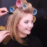 Blonde Mädchenhaarlockenwicklerrollen durch Friseur im Frisörsalon Lizenzfreie Stockfotos