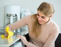 Blonde Mädchenreinigung in der inländischen Küche Lizenzfreie Stockbilder