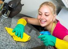 Blonde Mädchenreinigungsoberflächen an der Küche Stockbild