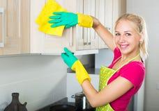 Blonde Mädchenreinigungsoberflächen an der Küche Stockfotos