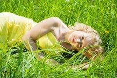 Blonde Mädchenreste auf Gras Stockfotos