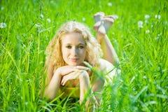 Blonde Mädchenreste auf Gras Lizenzfreies Stockbild