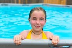 Blonde Mädchenschwimmen im Pool mit roten Backen Stockbild