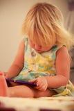 blonde Mädchenspiele mit Smartphonenahaufnahme Stockfotos