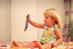 blonde Mädchenspiele mit Smartphonenahaufnahme Stockfoto
